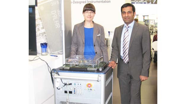 Vanessa Blumenstein, Regional Product Engineer Automated Test und Rahman Jamal, Global Technology and Marketing Director bei National Instruments an einem NI-STS-Halbleiter-Testsystem, das auf dem Systembus-Standard PXI basiert.