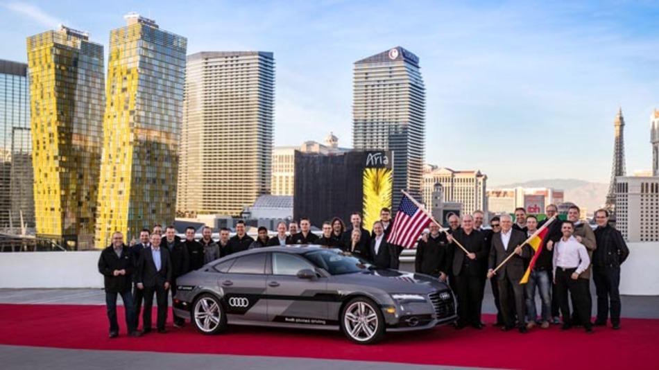 """Prof. Dr. Ulrich Hackenberg, Audi Vorstand für Technische Entwicklung (mit der deutschen Flagge), feiert mit dem Team, das die erfolgreiche Langstrecken-Fahrt ermöglicht hat, zusammen mit Ricky Hudi, Leiter Entwicklung Elektrik/Elektronik (mit der US-Flagge) und mit """"Jack"""", dem A7 quattro piloted driving concept."""