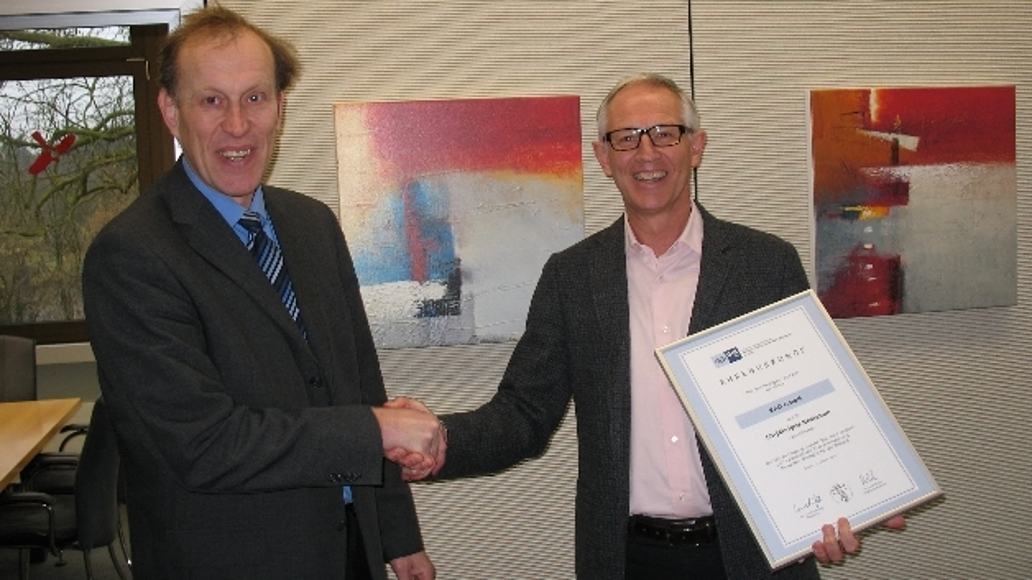 ^Guido Zakrzewski (links), stellvertretender Geschäftsführer der IHK in Essen, übergibt Manfred Sweekhorst (rechts), Geschäftsführer der EAO GmbH, eine Urkunde zum 50-jährigen Jubiläum der Firma.