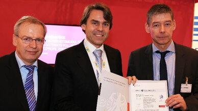 Bernd Kowalski vom BSS übergibt dias IT-Sicherheitszertifikat an Jacques Kruse Brandao, NXP, und Dr. Frank Schmidt, T-Systems