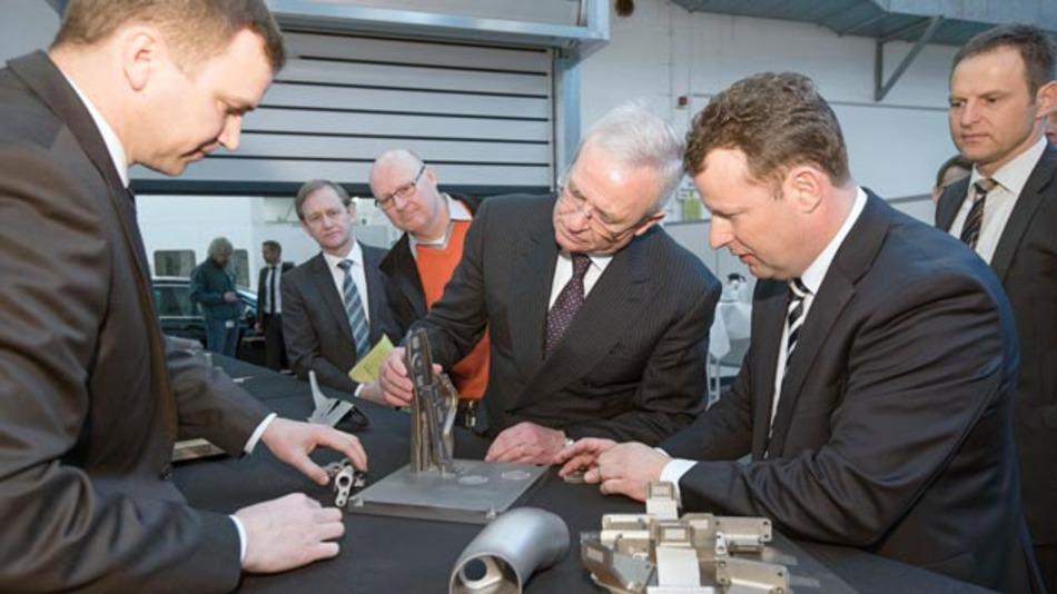 Prof. Winterkorn prüft in Wolfsburg ein mit dem metallischen 3-D-Drucker hergestelltes Bauteil.