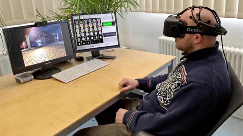 Ein Proband interagiert in einer Virtual Reality mit einem Computer.