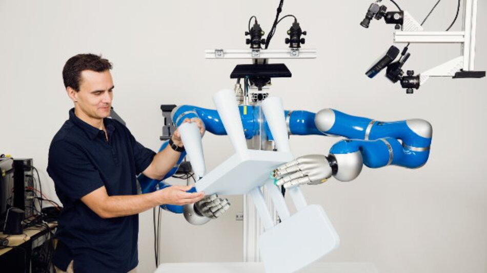 Prof. Jan Peters von der TU Darmstadt demonstriert einem zweihändigen Robotersystem die nötigen Schritte, um selbsttätig Möbel zu montieren.