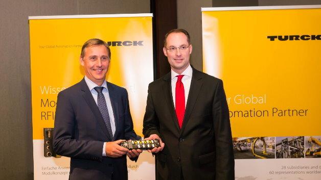 Jochen Bihl, Geschäftsführer von Bihl+Wiedemann, und Turck-Geschäftsführer Christian Wolf (rechts) mit einem Safety-/Standard-Block-I/O-Modul der Serie TBPN.