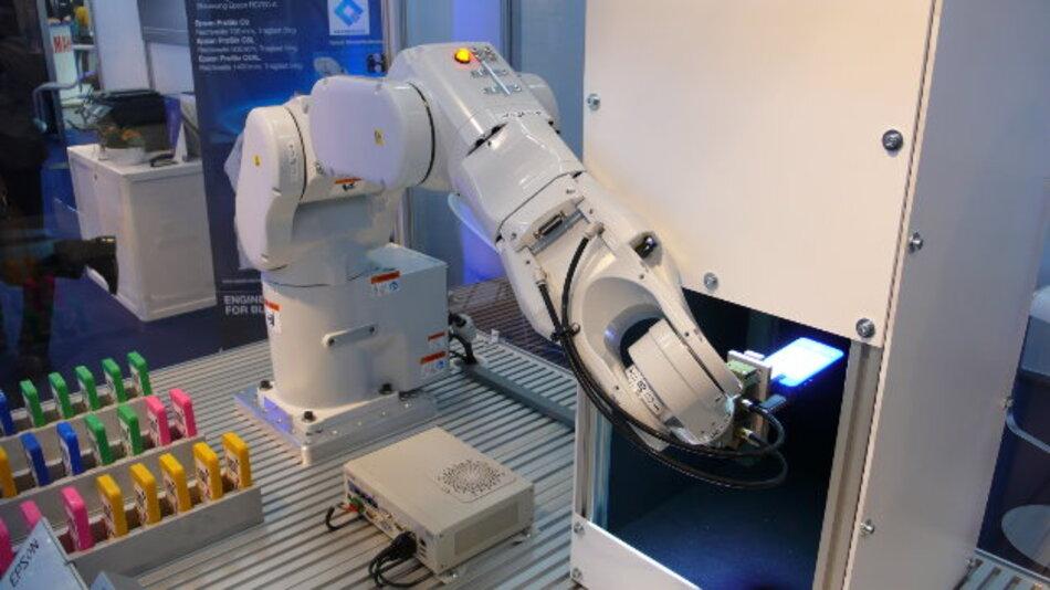 Auch der Sechsachs-Roboter C8 von Epson (Halle A3, Stand 438) kann Bauteile oder ganze Smartphones bei deren Endmontage einem Inspektionssystem zuführen. Hier …