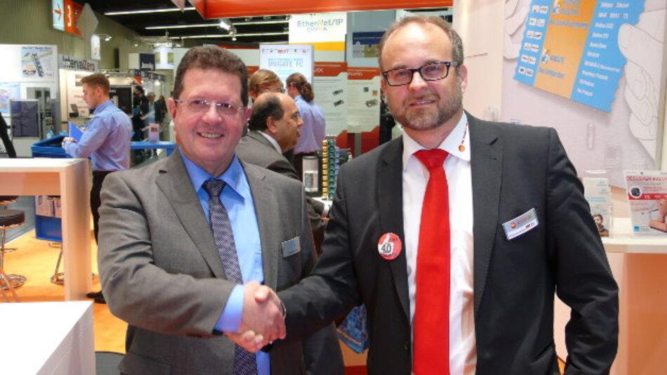Michael M. Reiter (links) von Deutschmann Automation und Siegfried Müller von MB Connect Line besiegeln auf der SPS IPC Drives die Partnerschaft.