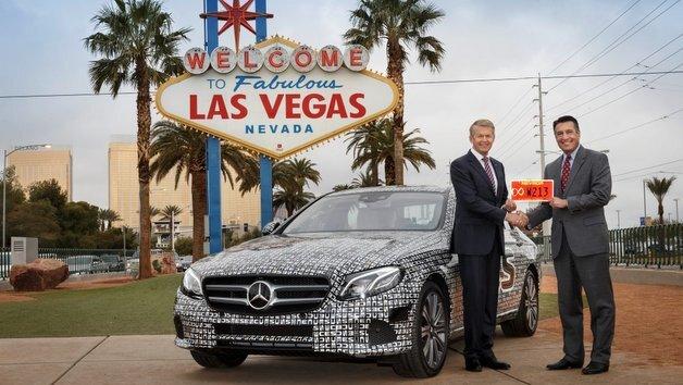 Brian Sandoval, Gouverneur von Nevada, (rechts)  übergibt Prof. Thomas Weber, Entwicklungs-Vorstand der Daimler AG, ein für autonomes Fahren reserviertes, rotes Nummernschild.