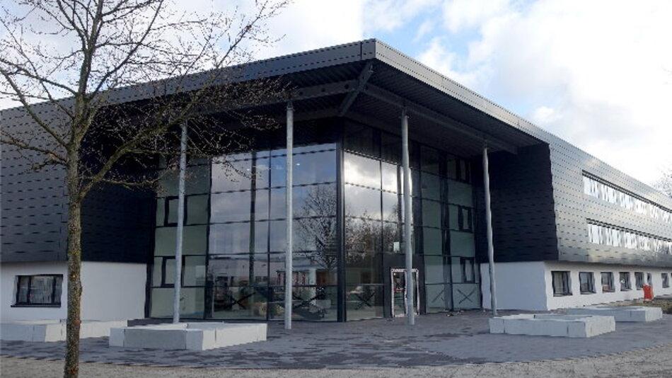 Das neue Viscom-Gebäude präsentiert sich mit einer klaren Architektur und einer modernen geometrischen Schlichtheit. Ein voll verglastes Eingangsfoyer verbindet zwei langgestreckte Baukörper.