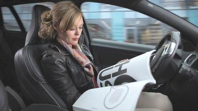 Frau in einem autonom fahrenden Fahrzeug