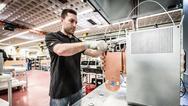 Das Bild zeigt einen Mitarbeiter am Prüfplatz, an dem die Powermodule einer Teilentladungsprüfung unterzogen werden. Diese Hochspannungsprüfung ist Bestandteil der Stückprüfung, die bei allen gefertigten Modulen durchgeführt wird.