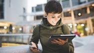 Frau mit Smartphone und Tablet