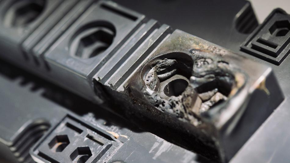 Kunststoffgehäuse eines Leistungsmoduls mit Materialschädigung (geschmolzenes Material) im Bereich der Lastanschlusslaschen.