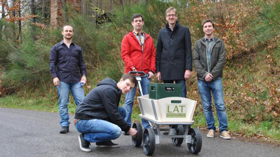 Mai-Tour-Test: Die Studenten Sergej Fabich (l.) und Matthias Hoffmann (kniend) testen mit Matthias Nienhaus (2.v.r.) und seinen Mitarbeitern Nico Haser (M.) und Robert Schwartz (r.) den intelligenten Bollerwagen.