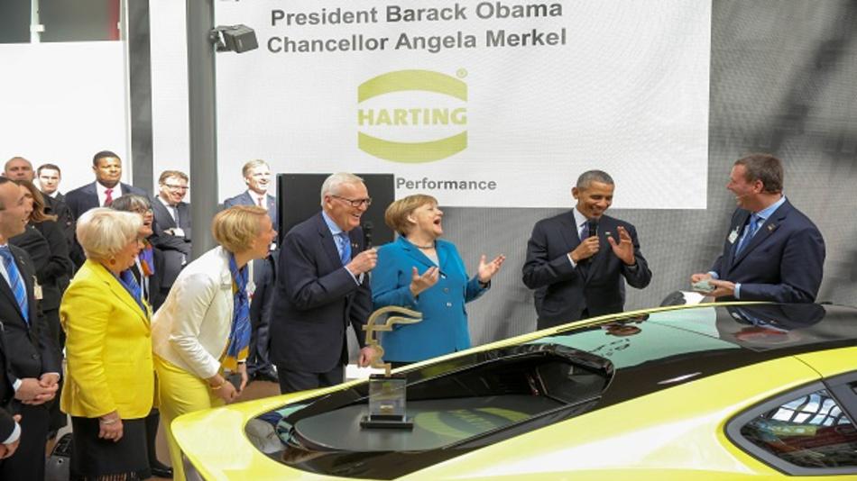 Angela Merkel und Barack Obama mit der Familie Harting (v.l. Margrit, Maresa, Dietmar und Philip) sind im Zuge der Verleihung des Hermes Awards auf dem Messestand von Harting.