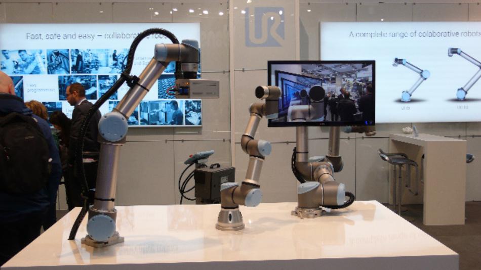 Beispielanwendung mit drei kollaborativen Robotern von Universal Robots: Der erste filmt den zweiten, und der dritte hält den Monitor, auf dem das Bild zu sehen ist.