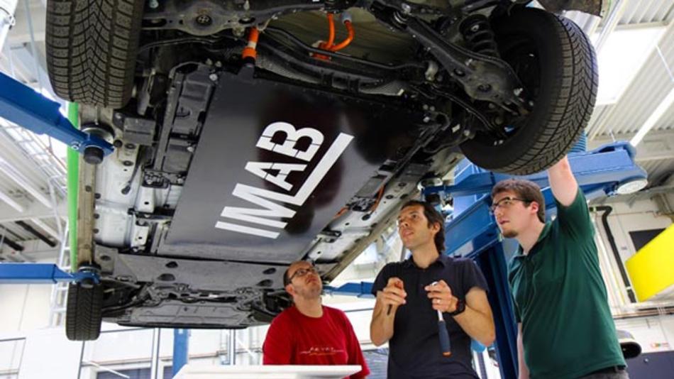 Die Ingenieure Jonas Wussow, Tamás Kurczveil und Tim-Hendrik Dietrich von der TU Braunschweig arbeiten unter einem Emilia-Golf am Induktivaufnehmer, dem so genannten Pickup.