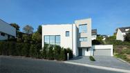 Für das Wohnhaus mit Hanglage hat in_design_architektur drei Kuben clever angeordnet: Sie spielen dabei mit Raumhöhen, Blickachsen und einer offenen Split-Level-Architektur.