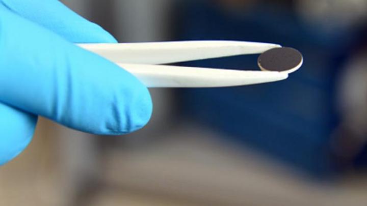 Eine Scheibe des weißen Lithiumgranat-Elektrolyten, beschichtet mit einer schwarzen Lithiumverbindung als Minuspgarol im Labor der ETH-Forschenden.