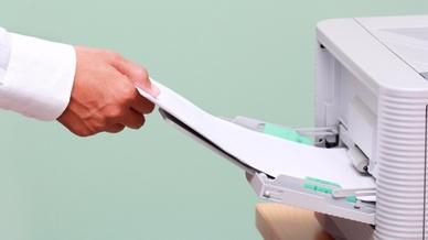 Man zieht Papier aus Drucker