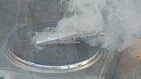 Eine Smartphone-Zelle wird auf einer Herdplatte überhitzt. Die Folge: Der Thermal-Running-Away-Effekt tritt ein, die Zelle öffnet sich und Batteriechemie tritt aus. Eingepackt in ein Smartphone würde sie Feuer fangen.