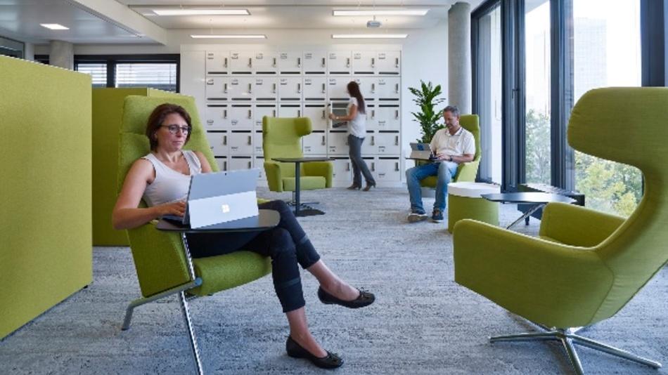 Im Hintergrund die Schließfächer der Mitarbeiter. Stark digitalisierte Arbeitsabläufe benötigen wenig Stauraum und machen das flexible Arbeiten möglich.