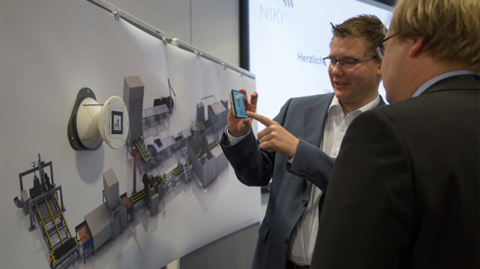Sascha Alpers (li.), FZI Forschungszentrum Informatik, zeigt Projektleiter Dr. Christoph Rathfelder (re.), Hahn-Schickard, die NIKI-4.0-Visualisierung mit Augmented Reality der Demo-Produktionsanlage mit Umweltsensor.