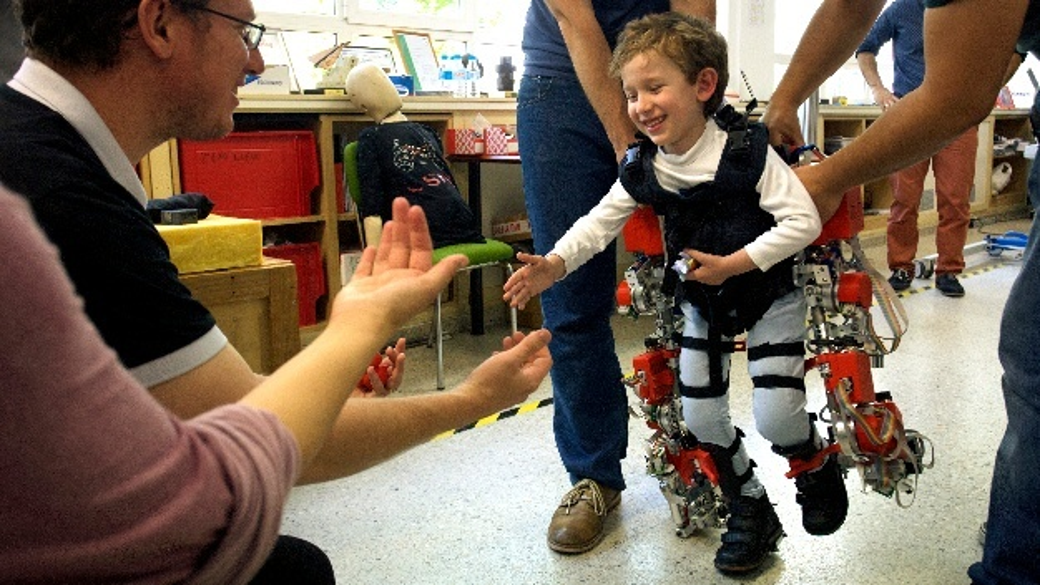 """Das im Experiment """"EXOTrainer"""" entwickelte Exoskelett bietet eine Therapiemöglichkeit für von Spinaler Muskelatrophie betroffene Kinder. Das gezeigte Kind macht die ersten Schritte seines Lebens."""