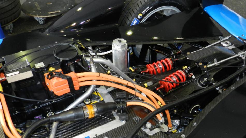 Mit SiC-Koponenten kann der Inverter der Rennwagen (an dem  die orangen Kabel angeschlossne sind) kleiner und leichter asgelegt werden als mit Bauelementen aus Silizium. Außerdem reduziert sich der Kühlaufwand deutlich, was dem Rennwagen zusätzlich Gewicht erspart.