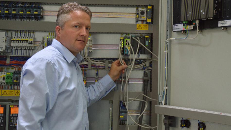 Frank Weiß, Geschäftsführer von Autech Tesla, vor einem Schaltschrank, der gerade in der eigenen Werkstatt zusammengebaut wird. Auch hier kommt der eWON-Fernwartungsrouter zum Einsatz.