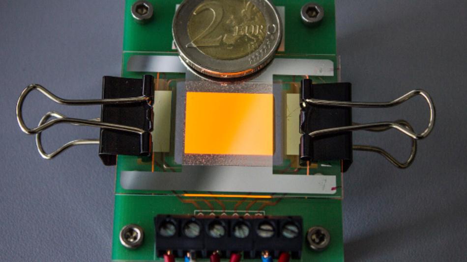 Orange leuchtende OLED auf einer Graphen-Elektrode. Die Zwei-Euro-Münze (oben) dient als Größenvergleich.