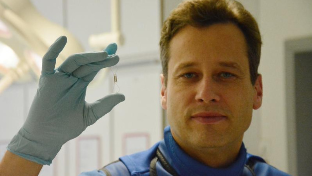 Dr. Andreas Zirlik hält den Blutdruck-Sensor vorsichtig zwischen zwei Fingern.