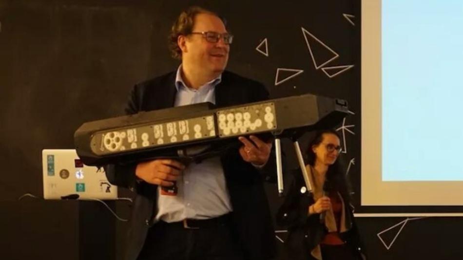 Martin Laarmann von der Make Munich präsentiert auch Kurioses aus Makerhand: Ein vollautomatisches Papierflieger-Maschinengewehr auf Basis eines Bosch-Akkuschraubers. Der Rest stammt aus dem 3D-Drucker.