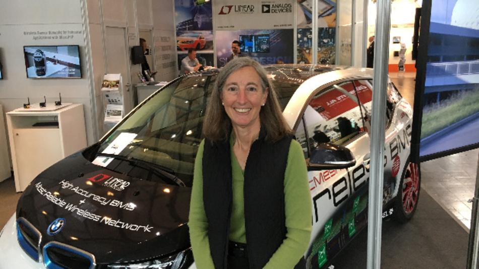 Joy Weiss von Analog Devices vor dem BMW i3, in den LION Smart das drahtlose Batterie-Management-System auf Basis der BMS-ICs von Linear Technology und dem SmartMesh von Dust Networks integriert hat.