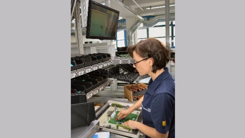 """Miroslawa Schneider von Ziehl-Abegg SE bestückt eine Leiterplatte, der digitale Arbeitskollege """"Schlauer Klaus"""" schaut ihr über die Schulter"""