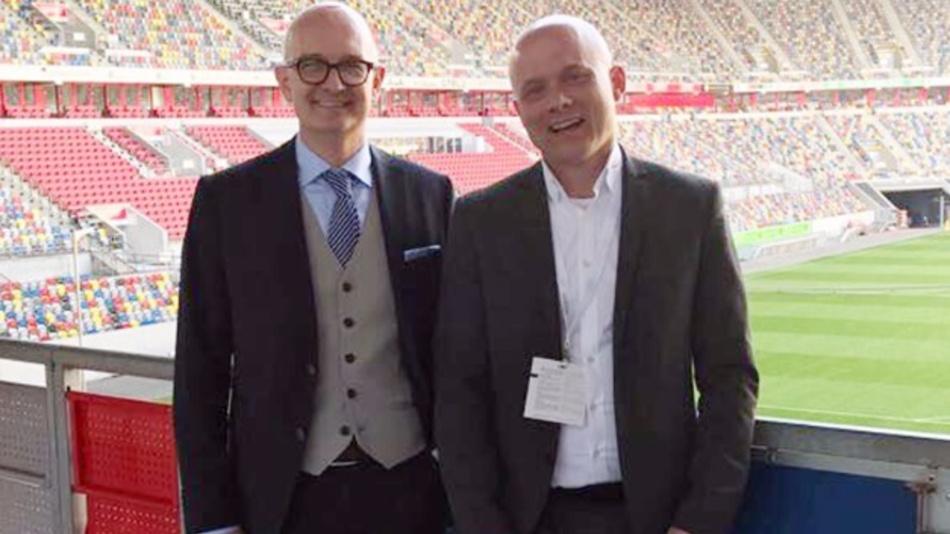Anpfiff für eine zukunftsträchtige Kooperation: Raphael Eckert, Group Sales Manager GS Yuasa Germany und Thilo Hack, Leiter Ansmann Energielösungen (v.l.n.r.) , im Stadion von Fortuna Düsseldorf. Als offizieller Teampartner von F95 Fortuna Düsseldorf, stattet GS Yuasa den Mannschaftsbus mit Batterien aus.