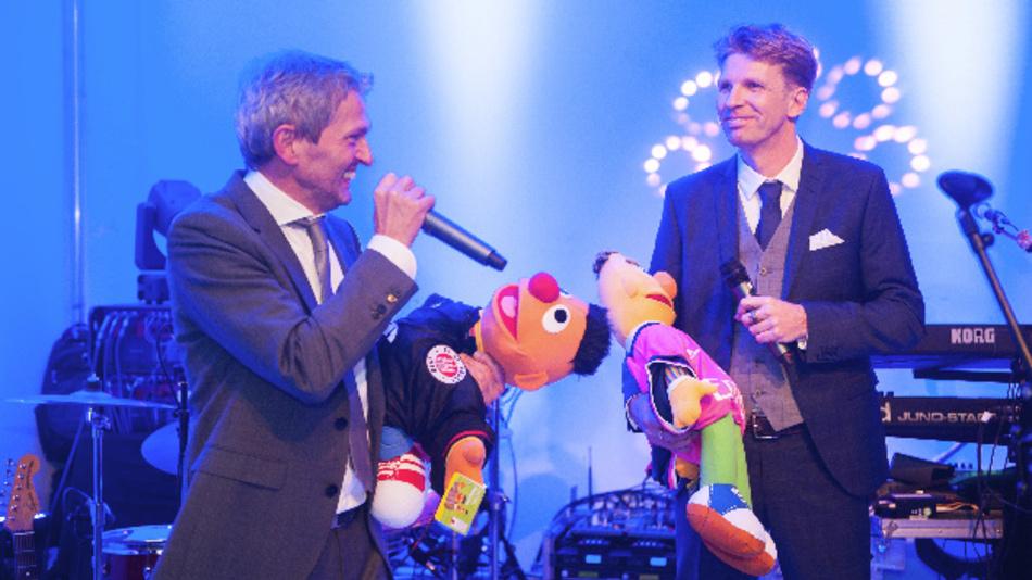 Matthias Fricke und Manfred Garz (v.l.n.r) feiern das 25jährige Bestehen Ihres Unternehmens mit Ernie und Bert.