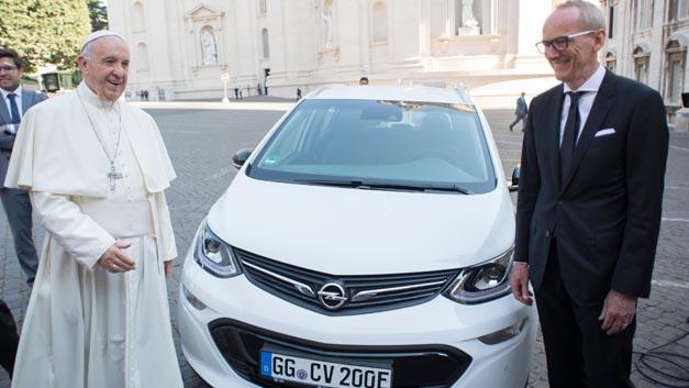Opel-Chef Dr. Karl-Thomas Neumann überreicht einen neuen Ampera-e an Papst Franziskus.