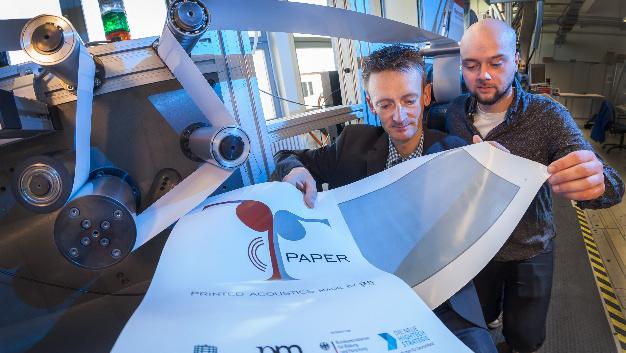 Projektleiter Dr. Georg Schmidt (links) und Student Robert Eland mit einem Probedruck an einer Rolle-zu-Rolle-Druckmaschine im Labor der Professur Printmedientechnik.