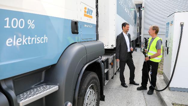 Michael Weihrauch, Leiter Logistik Porsche Leipzig, und ein Speditionsmitarbeiter stehen vor einer vollelektrischen 40-Tonnen-Sattelzugmaschine und einer Ladesäule.