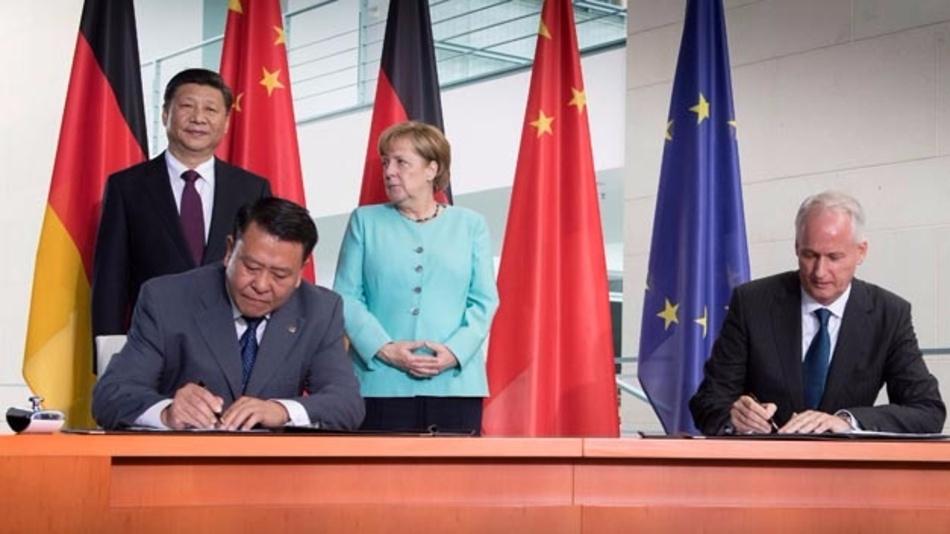 Xu Heyi, Vorstandsvorsitzender der BAIC Group (links) und Hubertus Troska, Vorstandsmitglied der Daimler AG (rechts) unterzeichnen Rahmenvereinbarung im Beisein von Bundeskanzlerin Dr. Angela Merkel und des chinesischen Staatspräsidenten Xi Jinping.