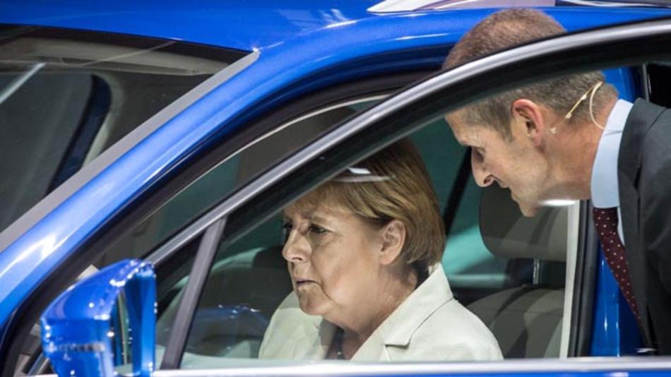 Bundeskanzlerin Angela Merkel saß am 17.09.2015 in Frankfurt/M. (Hessen) nach der offiziellen Eröffnung der 66. IAA am Stand von Volkswagen am Steuer eines Hybridfahrzeug vom Typ Tiguan GTE, den sie von VW-Markenvorstand Herbert Diess (r) erklärt bekam.