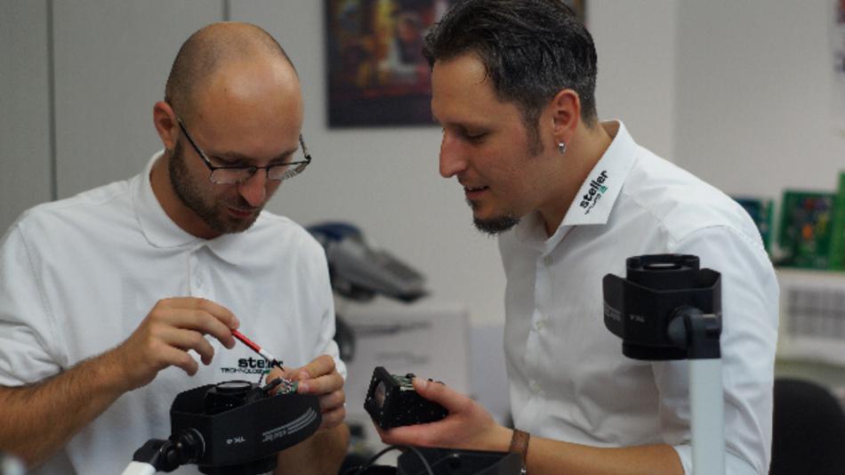 Produktionsmitarbeiter Alexander Schenke beim Erklären einer Platine des Kamerasystems TK4, rechts Chef Johannes Steller.