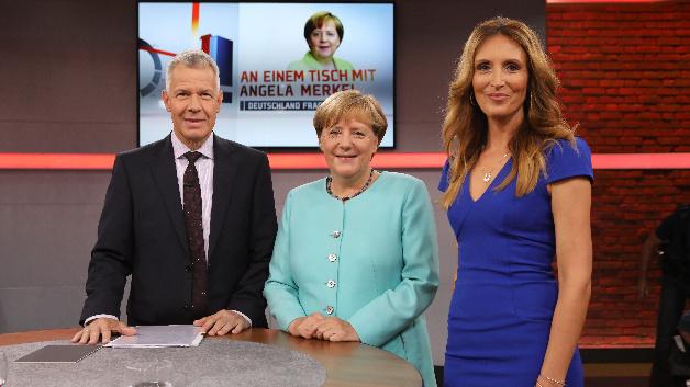Bundeskanzlerin Angela Merkel (M, CDU) steht zwischen RTL-Chefmoderator Peter Kloeppel und Co-Moderatorin Roberta Bieling.