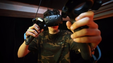 Ein junger Mann taucht in einem Virtual-Reality-Raum in Immenstadt (Bayern) mittels einer VR-Brille in eine virtuelle Welt ein.