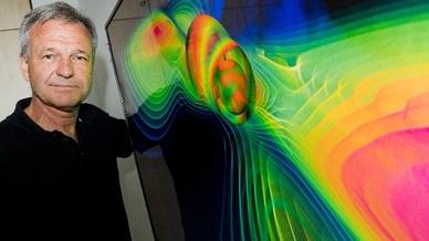 Karsten Danzmann vor einer Visualisierung von Gravitationswellen