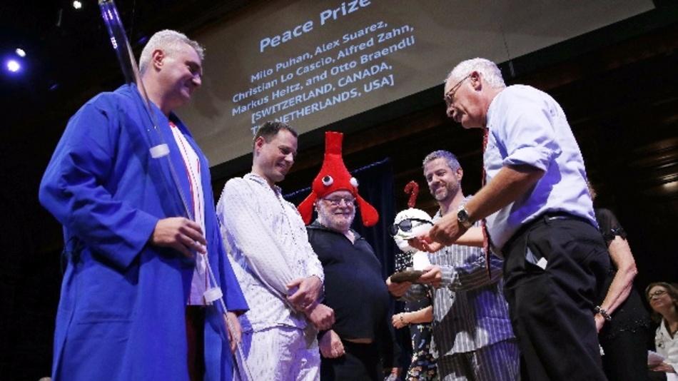 Alex Suarez (l-r), Christian Lo Cascio, Markus Heitz, Milo Puhan erhalten den Ig-Nobelpreis von Nobelpreisträger Oliver Hart (r)  - für die Entdeckung, dass das regelmäßige Spielen eines Didgeridoos gegenSchlafbeschwerden und Schnarchen helfen kann.