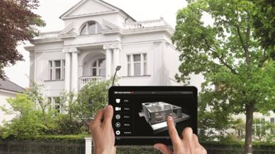 Person steht mit Tablet vor einer Villa und steuert aus der Ferne das Sicherheitssystem.