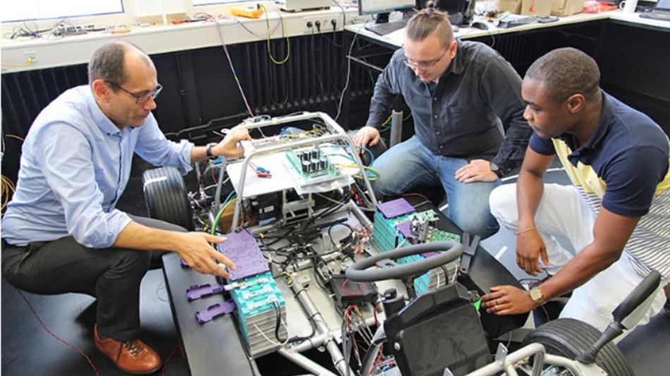 Prof. Alexander Kuznietsov, Tilman Happek und Frank Tanenkeu (von links nach rechts) arbeiten am hochschuleigenen Elektrofahrzeug, in dem das Batteriemanagementsystem getestet wird.