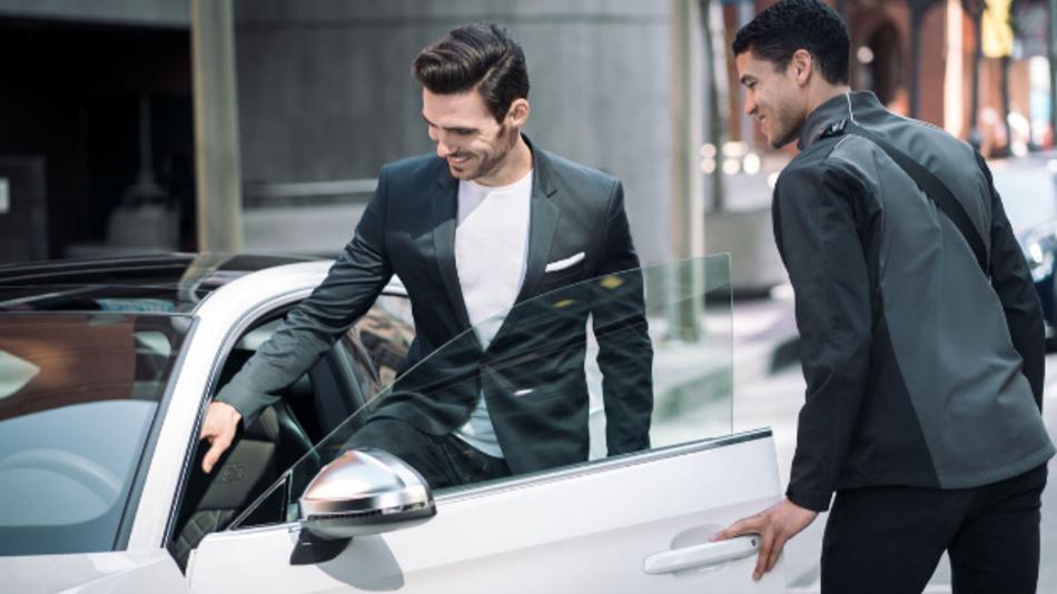 Ein Concierge übergibt dem Kunden das ausgewählte Fahrzeug.