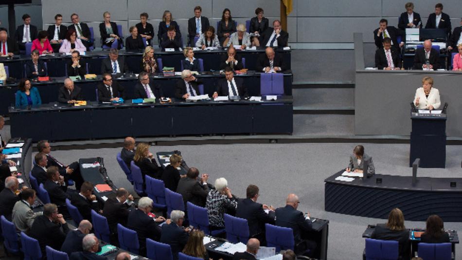 Bundeskanzlerin Angela Merkel bei einer Debatte im Deutschen Bundestag, links die Bank der Bundesregierung, 2014. CC BY-SA 3.0 de